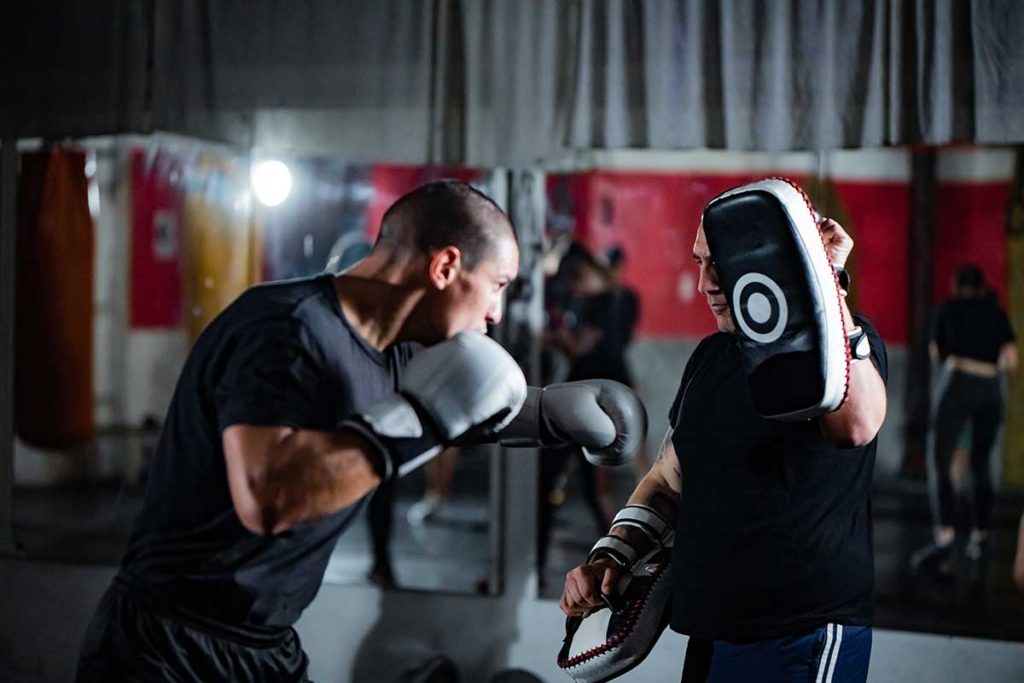 Adult man boxing with a trainer