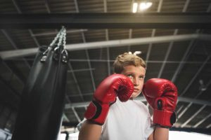 Young boy boxing with red gloves