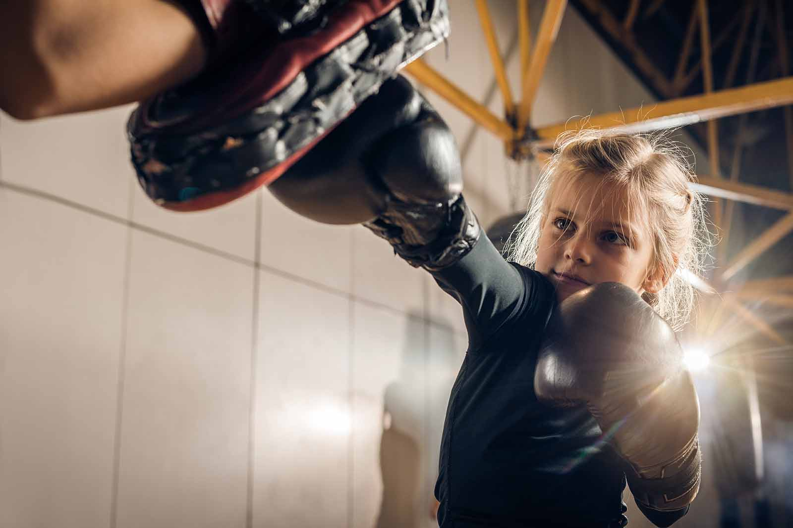 Young girl boxing with a trainer