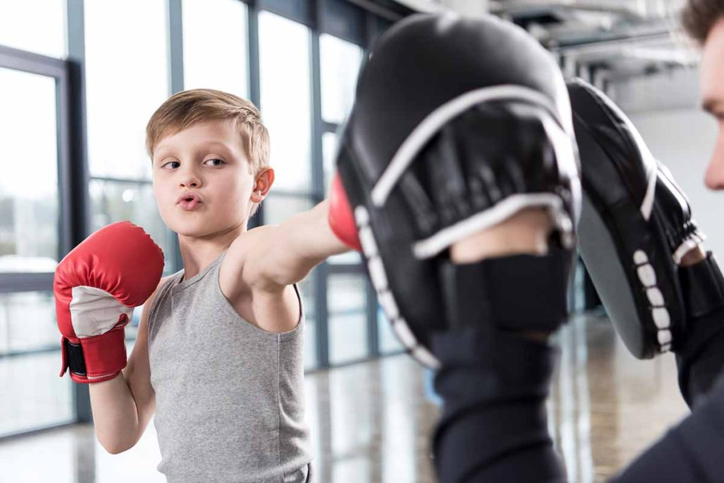 Boy boxing with a trainer